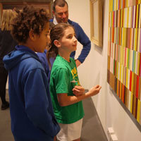 Photograph of young boy and girl looking at artwork