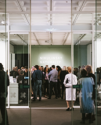 A photograph of the main entrance of the gallery, showing a crowd of people